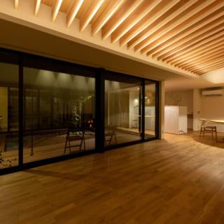 夜になるとがらりと印象が変わるK邸のLDK。キッチンはトップの立ち上がりを高めにし、リビングから見えすぎないようにした。照明は計算しつくされた配置で影も美しい。床材に選んだのは温かみのあるオーク材。天井の化粧垂木が空間にリズムを生み、居心地がいい空間だ