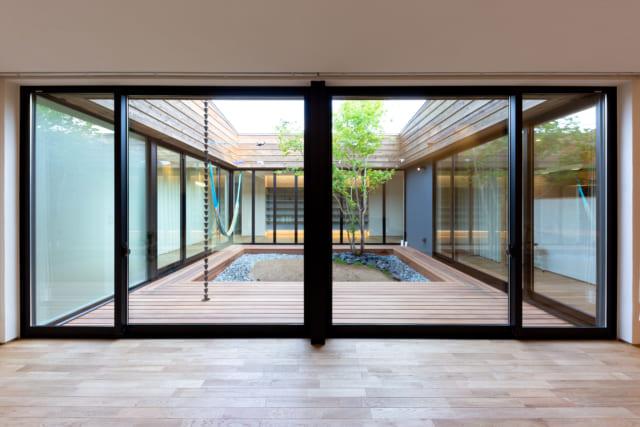 室内の床とウッドデッキは同じ高さで繋がる。ウッドデッキにはメンテナンスフリーの素材を使用した。中庭にも回遊性を持たせることで、家は大きなワンルームのように使える。家族の気配も感じられるほか、「庭を通して自分の家を眺められるのがいいですよね」と堀井さん