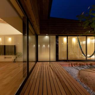 キッチン前のウッドデッキから玄関方向を見る。中庭は透明なガラスで囲われているが、玄関の真正面にあたる1枚だけはフロストガラスとした。ガラスの曇りによって玄関から内部空間が丸見えになることを防いでいる。また、玄関からリビングに続く部分には引き戸を設けた