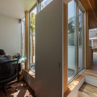 仕事場からLDKなどの居住スペースを見たところ。仕事場の横には、植栽、砂利敷きの中庭を設けており、また居住スペースよりも床のレベルを下げることで、空間をさりげなく仕切っている