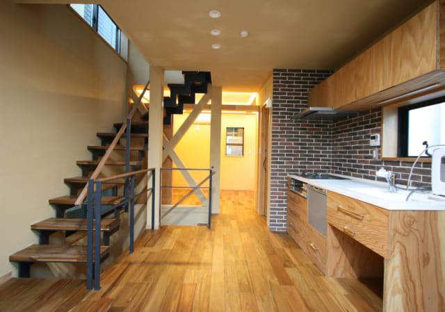 2階・子世帯DKからご主人の寝室を見る。引き戸を全開すれば2階全体が大きな1室空間に。ハイサイド窓など、効果的な窓計画との相乗効果で通風・採光・開放感は抜群。床はオイルステイン仕上げの無垢のアカシア、キッチン以外の壁は消臭・調湿作用などをもつシラスの塗り壁