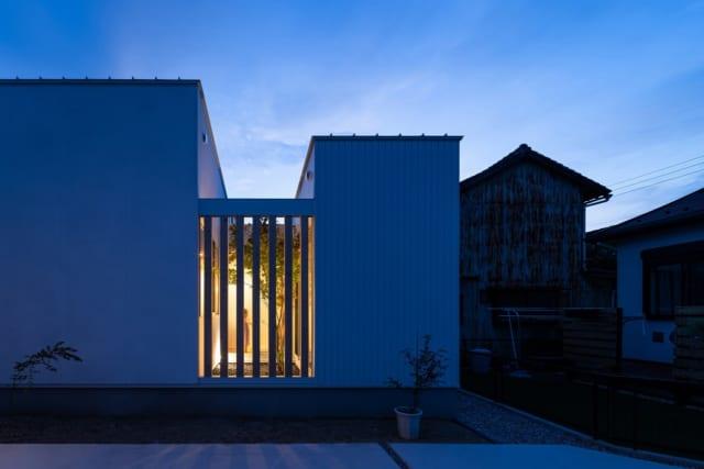 """木格子の奥の中庭から漏れ光る灯りや、植栽のシルエットが美しい外観。右側が仕事場の""""箱""""、左側がLDKの""""箱""""で、中庭を介して繋がっている"""