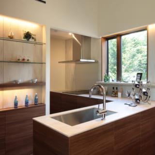 オーダーでしつらえたキッチンは、壁際のカウンターからシンクスペースが伸びたT字型。北の庭の緑が見える窓もあり、南の窓から入る風が気持ちよく抜ける。ディスプレー棚の先にはパントリーも。床下暖房システムのエアコンは、生活空間から見えにくいパントリー内に設置している