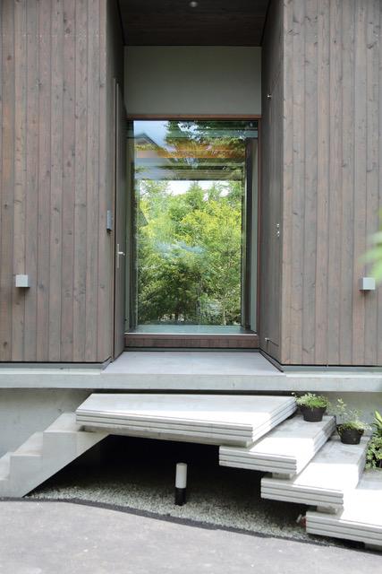 玄関ポーチまで来るとガラスの壁を通して視線が抜ける。庭の緑をのぞき込むような視界が楽しい