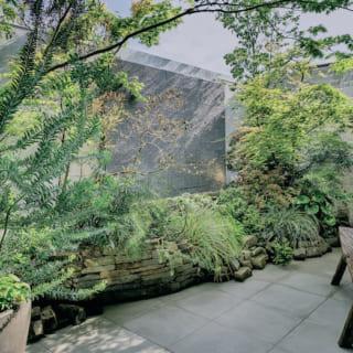 個性的なアイテムで彩られた2階ガーデンテラス。木々の合間には滝が流れる石のアクアウォールがあり、光、緑、水音など、心安らぐ自然を感じながらゆったりとくつろげる
