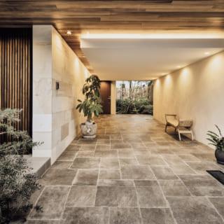 1階ガレージ。ニュアンスのあるタイルや板張り天井、植栽などのアースカラーでまとめられ、邸内同様にリゾート感たっぷり。奥の木製ドアはNさまの自邸への玄関で、ここから2階に上がると住空間が広がる。手前のドアは賃貸住戸の門扉。賃貸も人目を引く洒落た佇まい