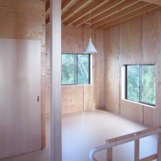 四角い自宅部分の2階、寝室。扉の奥には洗面室と浴室がある。寝室は将来、仕切って二部屋としても使えるようにした。店舗用の棚受け金物を設置し、その時々に合わせて棚を付け替えられる。コンパクトな部屋であるが柔軟な使い方でうまく住みこなすための工夫が施されている