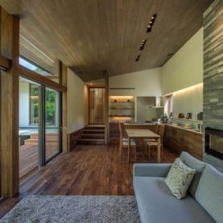 リビング側からダイニング、キッチンを見る。リビングのソファに座ると目の前に爽やかな緑が広がり、心が解き放たれるかのよう。床はウォルナット、天井や柱は床のトーンに合わせた色で塗装。少し赤みのある木材の効果で、外の緑がいちだんと映える