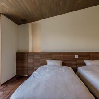 主寝室も、高原の別荘らしく天井を板張りに。壁の凹んだ部分は通風用の出窓。正面をふさいでサイドにスリット窓を入れることで、風通しとプライバシー確保を両立