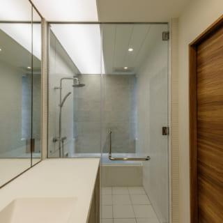 洗面室からバスルームを見る。洗練されたガラスのドアと仕切りでホテルライクな空間に