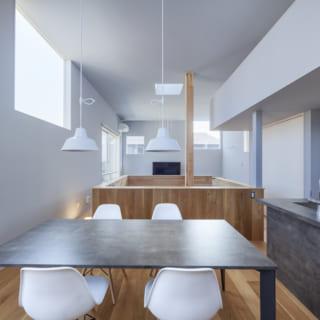 2階ダイニングスペース。壁がライトグレーなので白い照明や椅子が映え、洗練された北欧風の空間に仕上がっている。写真右はキッチン。キッチンカウンターはGRAFTEKTのもの。テーブルはキッチンに合わせてセレクトした