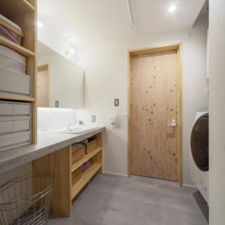 たっぷりの収納を設けた1階洗面室。奥の扉の先はバスルーム。床はモルタル調のシートを張っている