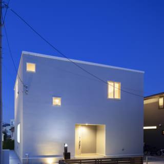 外観夕景。四角い箱からぽつぽつと光が漏れ、現代アートのオブジェのよう