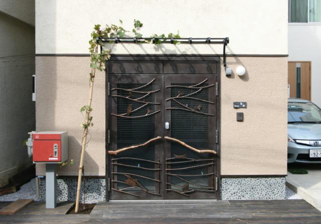 玄関ドアはエイジング塗装し、アイアンより軽くて扱いやすいロートアルミを取り付け、アンティーク風の味わいをプラス。引き手はIさまが見つけてきた流木。基礎部分にあしらった石はIさまが選んだもの。かわいいブドウの葉に彩られ、存在感のあるファサードとなっている