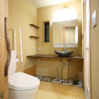 1階洗面&トイレ。カウンター周りは「坪庭風にしたい」との要望に応え、石の洗面ボウルや砂利石で仕上げた