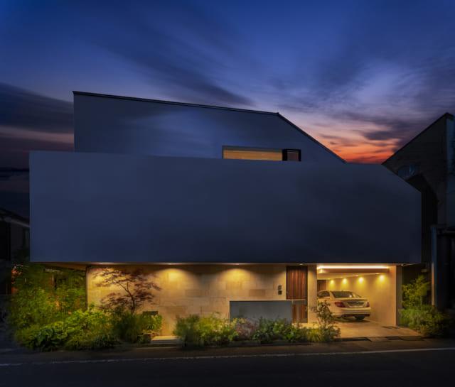 外観夕景。desusは「内と外のつながり」を生むことが得意なだけあり、外構デザインのセンスも抜群。バランスのよい植栽と照明演出で、人目を引く美しい佇まいとなった