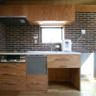 2階・子世帯のキッチンは家電配置や収納の要望に応えるため、オリジナルで造作。木製部分は床のアカシアと色調を合わせている。周囲の壁は汚れが気になりにくい、少しざらついた温かな風合いのレンガタイル