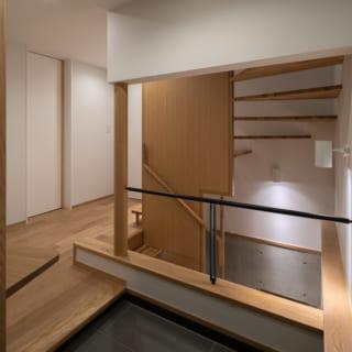1階玄関。地下1階、2階への階段は壁で隠さず、オープンに。玄関に入ったときの視線の抜けと明るさを確保