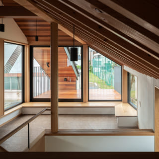 2階リビングとテラス。窓際にベンチがあるリビングは3面が窓で、抜群の開放感。齋藤さんは室内天井と同じレッドシダーを張った屋根をテラスにつくり、その屋根で家を支えるというアイデアで耐力壁を不要に。おかげで大きく窓を取ることができた