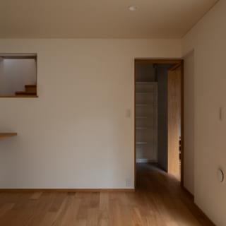 地下1階の主寝室。地階だが写真右の大きな窓越しにドライエリアがあり、光がふんだんに入る。風も、写真左の壁上部にある小窓から抜けて快適。出入口の引き戸の奥に進むとガレージにつながる出口があり、万が一、夜間に災害が起きても1階の玄関まで上がらずに避難可能
