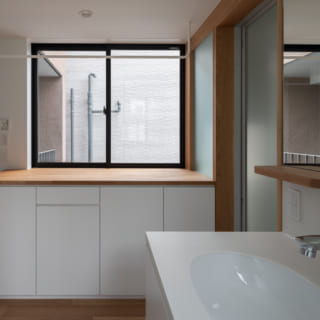 1階の洗面室は、洗濯にまつわる一連の家事が完結するランドリールーム的なスペース。窓の上部は物干しバー、その下の収納棚には開閉式のアイロン台もある。収納はこのほかにも設けられており、お風呂上りに着る家族の普段着などを置いておくことができる
