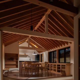 2階リビングからダイニングを見る。木の山型天井、段差のある造りなど、ヴィラ風の洒落た空間でくつろげる