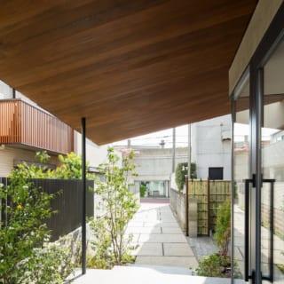 玄関から道路方向を見る。道路から伸びたアプローチはシダレモミジなどに彩られ、茶室の露地の役割も果たす