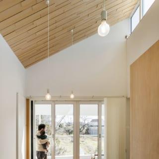 リビングの勾配天井には厚みの異なるシナベニヤを並べて張り、立体感のあるデザインに仕上げている。そこへ上部の窓からの光が反射し、リビングをやわらかく明るくしてくれる