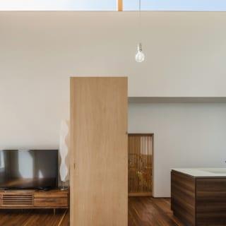 キッチンの裏にある和室へは、茶室のように丈の低い格子戸をくぐって行き来する
