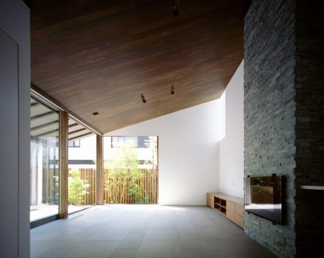 1階LDKのキッチンからダイニング・リビングを見る。板張り天井や石をあしらった暖炉は、軽井沢の別荘のような高級感。奥のリビングは東と南の大きなコーナー窓があり、庭との一体感は抜群。右奥の壁には、上方からの光を入れるハイサイド窓も設置