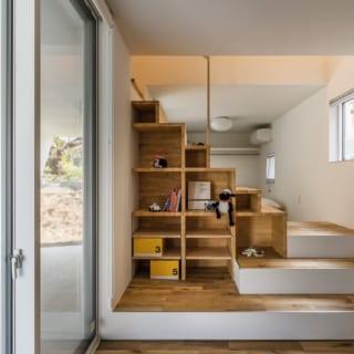 リビング階段は側面に棚を造作して、階段箪笥として利用。また、1階の2部屋の間仕切りの役割も担わせている