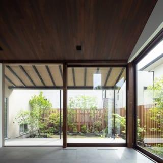 1階リビング。2面を大きく開口した設計と広縁が活き、リビングにいながら庭の一部にいるような開放感。窓のロールスクリーンや網戸は完全に引き込むことができ、広縁や庇の構造は細い鉄骨を使用。庭とのつながりや景色を邪魔しない、ディテールにこだわった造りはさすが