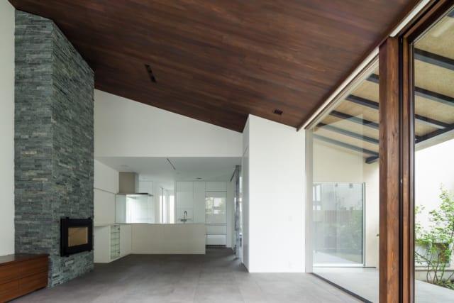 1階LDKのリビングからキッチン・ダイニングを見る。キッチンから右に進むと玄関ホール。床は玄関ホールと同じタイルで仕上げ、統一感を出している。奥野さんが採用する床下冷暖房システム・パッシブ冷暖はタイルの床も十分に温まり、温度ムラもなく、熱環境は通年快適
