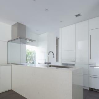 1階キッチンはフルオーダー。カウンターのワークトップや側面はクォーツ。家電を置ける背面収納の一部はビルトインの冷蔵庫。生活感のないすっきりと洗練されたキッチンだ。奥はパントリーや勝手口、その先にはアウトドアグッズ用の収納スペースがある