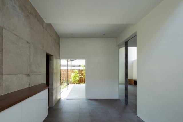 1階玄関ホール。和洋どちらにも合う内装だが、茶室の躙り口にちなんで小さめにつくった窓、黒いタイルの床や掛け軸をかけられる漆喰壁などで茶の湯の世界を表現。1階は一辺に玄関ホールと茶室、一辺にLDKが配されたL字型。左の出入口の先は茶室、右に進むとLDKが広がる