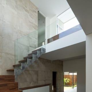 広々した玄関ホールは、のびやかな吹抜け空間。手すり壁をガラスにした2階通路と窓越しの空も見通せる