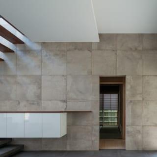 玄関ホールで茶室の出入口を見る。邸内に入ったとき茶室に意識が向かうよう、茶室側に階段や窓を配し、壁もこの面だけ表情のあるベージュのタイル壁にしている。階段の側面もエイジング塗装し、「わびさび」を感じさせる空間に