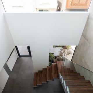 2階通路から1階の玄関ホールを見る。階段の手すりはガラスで、階段そのものの美しさや浮遊感が引き立つ。玄関ホールは茶室の露地としての役割を果たすスペースだが、上質なモダン建築といった趣もある空間だ