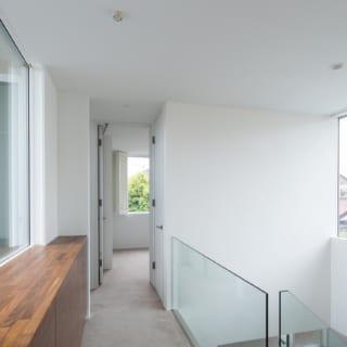 2階通路は吹抜けに面しており、両サイドには窓もあって抜群の開放感。奥は主寝室、左には水まわりとバルコニー。ほか、2階にはゲストルームもある