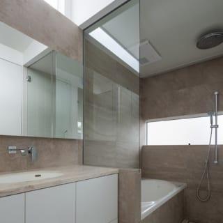 ホテルのような2階の洗面室・バスルームはオリジナル。壁は統一し、浴槽側面も壁と同じ素材を張っている