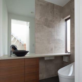 大きな鏡やスリット窓で明るさを感じられる1階トイレ。壁は吹抜けの玄関ホールと同じ素材を使用