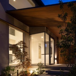 玄関夕景。ガラス張りの玄関は夜になると光の箱のように美しく、高級料亭のような佇まい