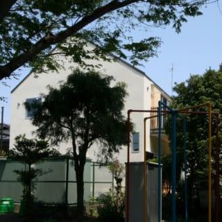 隣の公園から見るH邸。絵本に出てきそうな「おうち」そのままの外観が、のどかな公園の景色に馴染んでいる