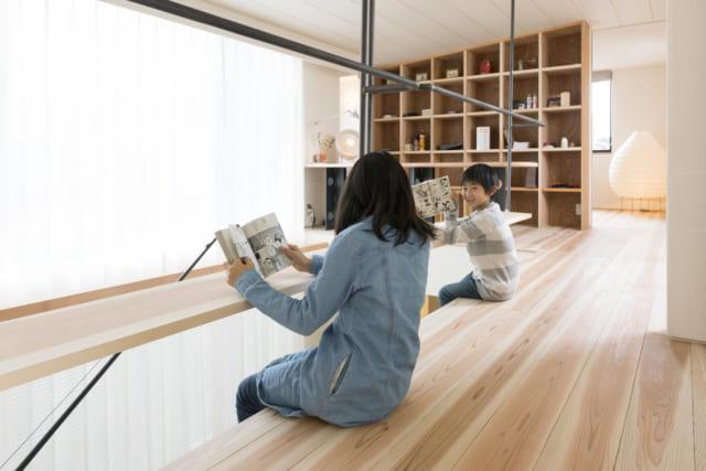 2階吹き抜け。廊下として使うホールも、ちょっとしたテーブルのように使える板を設けることで、空間の使い道がぐんと広がる。奥の本棚が壁がわりとなって、プライベートな空間である寝室を仕切る