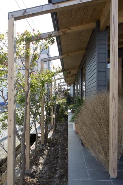 家と道路の境は植栽で緩やかに仕切る。軒下にも土間と同じタイルを貼り、室内との境目を曖昧にしている