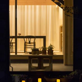掃き出し窓の外から土間、ダイニングを見る。帰る人を優しく迎え入れるような色合いの照明が印象的
