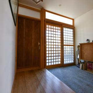 玄関。右に見える格子戸は新調した建具のひとつ。その隣のトイレへの扉や照明は前の家から引き継いだ