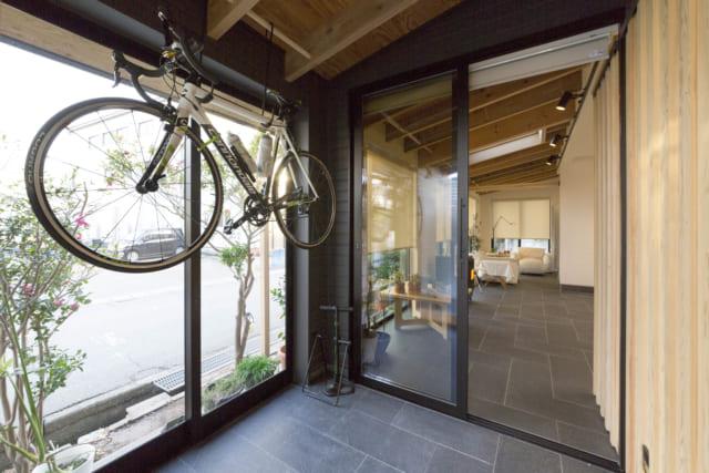 玄関と室内の間に位置する、雪や風が室内に吹き込むことを防ぐ風除室から土間リビングを見る。アプローチから玄関を通って風除室、通り土間の奥まで外壁や床のタイル、天井の梁が連続している。この空間が中間領域として際立つだけでなく、広さも感じられる