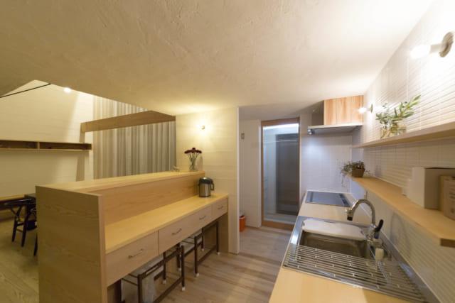 キッチン。キッチントップには青森ヒバの無垢材を使用。「母が料理することもあり、昔ながらの大皿料理を上げ下げするスペースが必要でした」と堀井さん。そこで背面キッチンにし、ダイニングとの間には目隠し替わりにもなる高めのカウンターを設置した