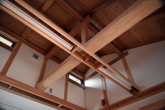 居間、化粧現しの梁を見上げる。梁は加工により、木材が持つ表情をより魅力的に引き出している。「木組みの家」というように、木材は金物を使わず木と木を組んで固定しており、その組手を眺めるのも楽しい。解体時には木材をきれいにばらすことができ、次の世代に引き継げる